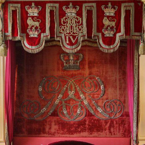 Detail of The crimson velvet lambrequin pelmet and backboard